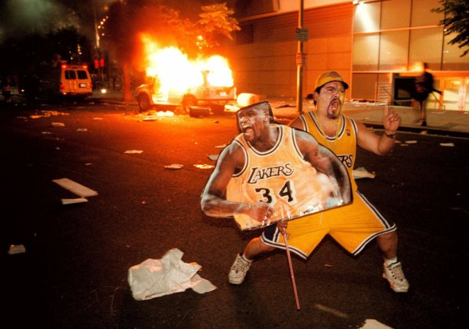A fan celebrates outside the  Staples Center with a large cut out of Shaquille O'Neal as a news vehicle burns after the Los Angeles Lakers defeated the Indiana Pacers in Game 6 of the NBA Finals  Monday, June 19, 2000 in Los Angeles. A celebration of the Lakers' first championship in 12 years deteriorated into mayhem as hundreds of fans torched two police cars, vandalized businesses and set dozens of small bonfires in streets. (AP Photo/Inland Valley Daily Bulletin, Stan Lim) ORG XMIT: CAONT106